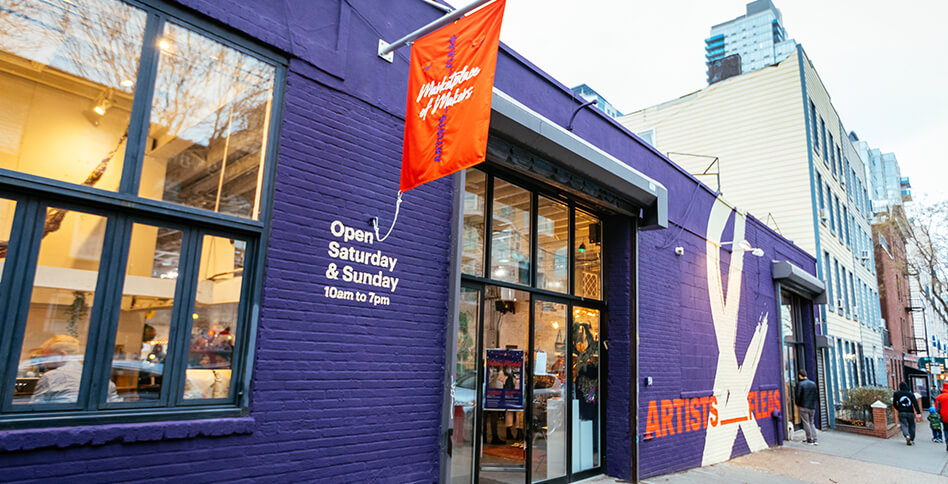 Storefront of Artists & Fleas Williamsburg with red flag and purple ampersand mural