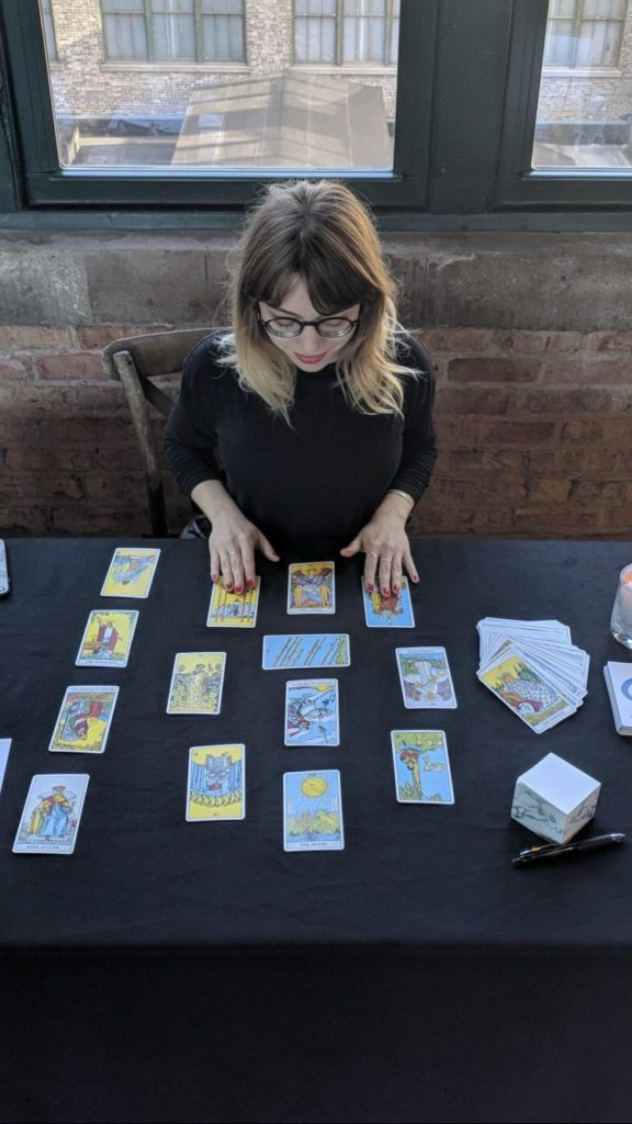Woman reading tarot cards laid out on a table.