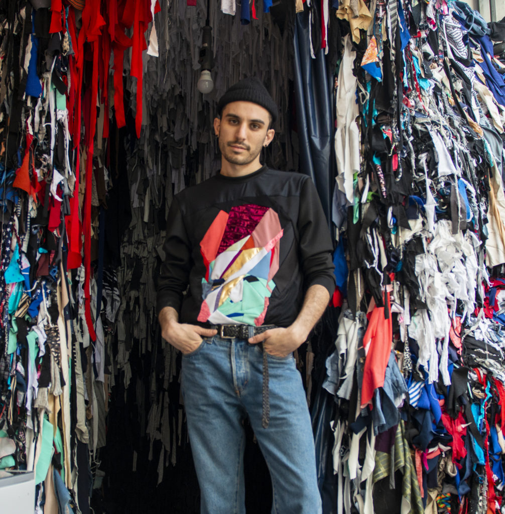 Zero Waste Daniel in front of recycled and reclaimed fabric scraps in his Williamsburg, Brooklyn studio