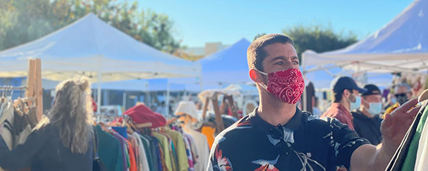 Man wearing a red face mask shopping at an outdoor market