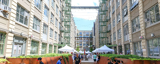 A pop up market with white tents and people milling about in the courtyard at Industry City